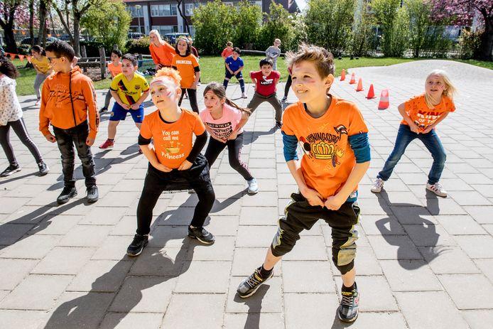Een dansworkshow in het zonnetje, de kinderen van de groepen 3 en 4 van De Regenboog in Tiel vermaken zich uitstekend tijdens de alternatieve Koningsspelen.