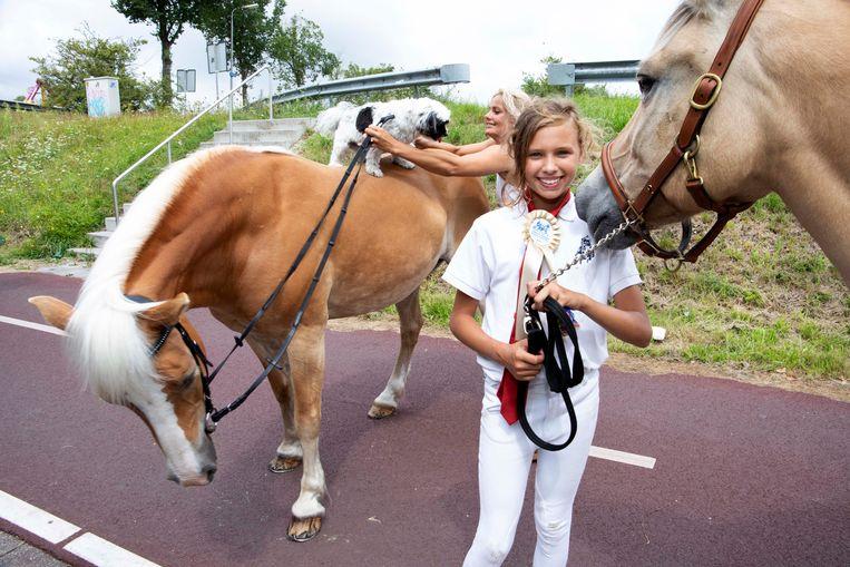 Mariska (33) zet haar hond Leila op het paard Ginger. Vooraan staat Chelsea (11).  Beeld Martijn van de Griendt