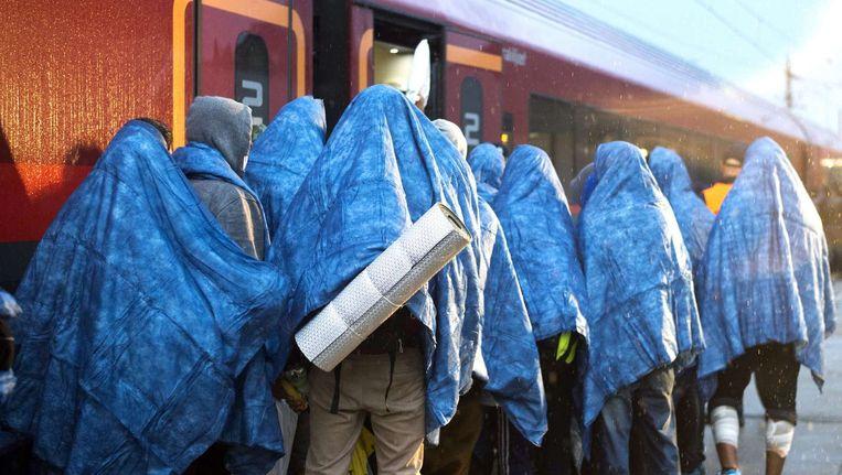 Vluchtelingen stappen in de trein richting München. Beeld Reuters
