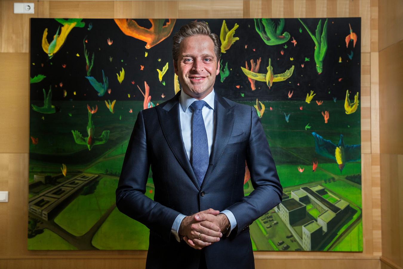 Minister Hugo de Jonge (Volksgezondheid) poseert voor een schilderij van zijn broer, dat op de werkkamer van De Jonge op zijn departement hangt