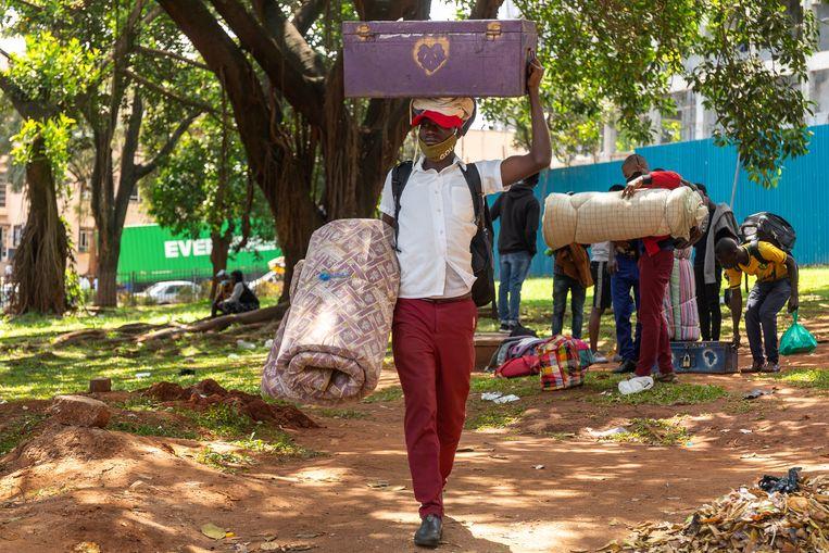 Een man is met zijn matras en wat bezittingen op weg naar het busstation van Kampala. Hij wil terug naar zijn ouderlijk huis, hij vreest een nieuwe economische klap door de covidcrisis.  Beeld Badru Katumba