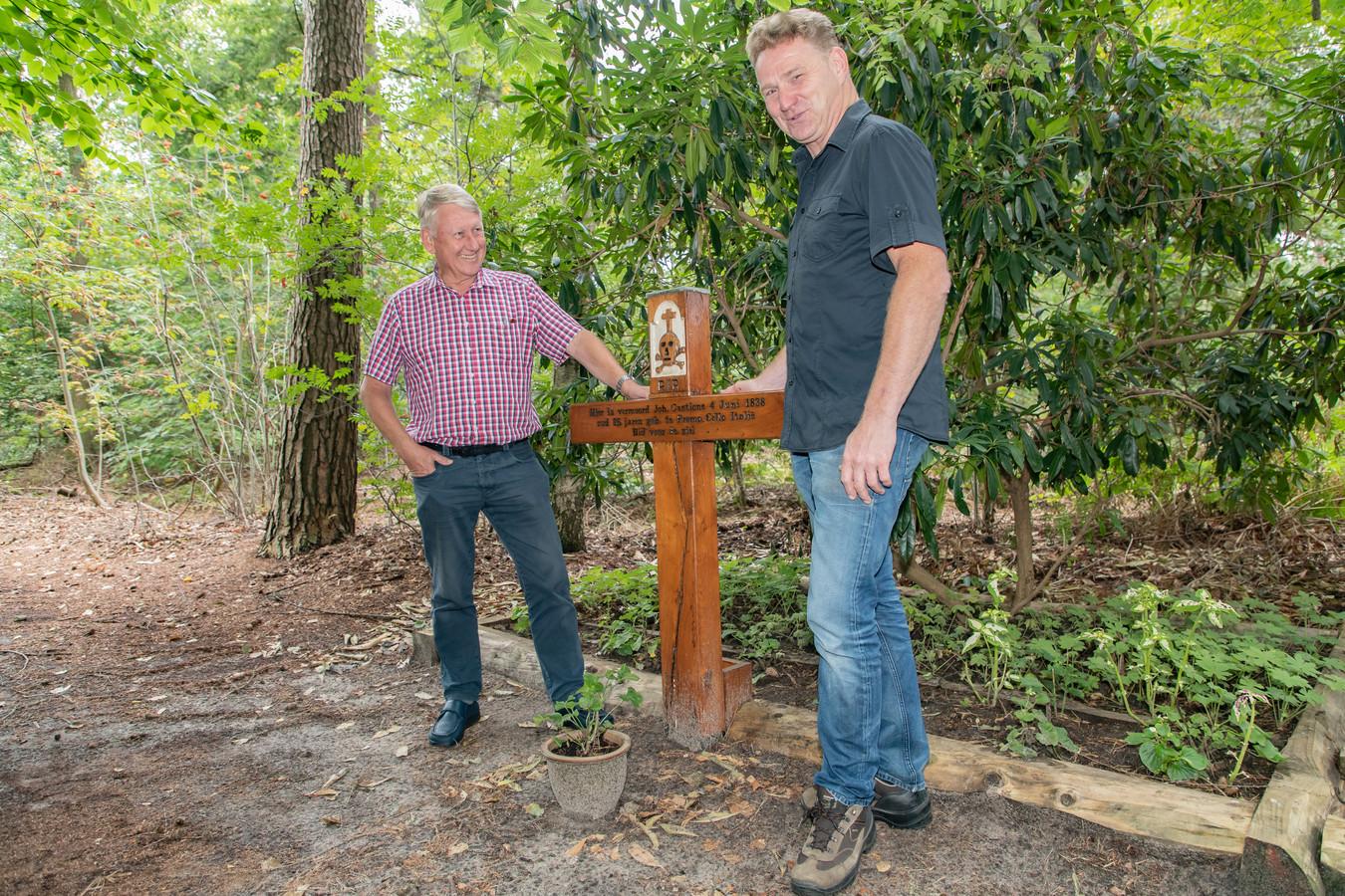 Leon Vingerhoeds (donker overhemd) en Theo Cruijff bij kruis in het bos.