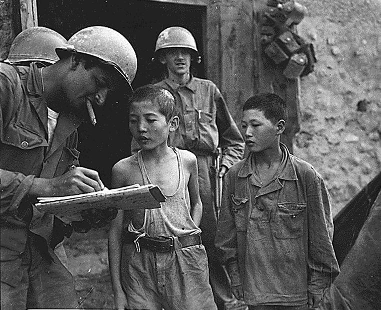 Een Amerikaanse soldaat verhoort in 1950 twee Noord-Koreaanse jongetjes. Beeld afp