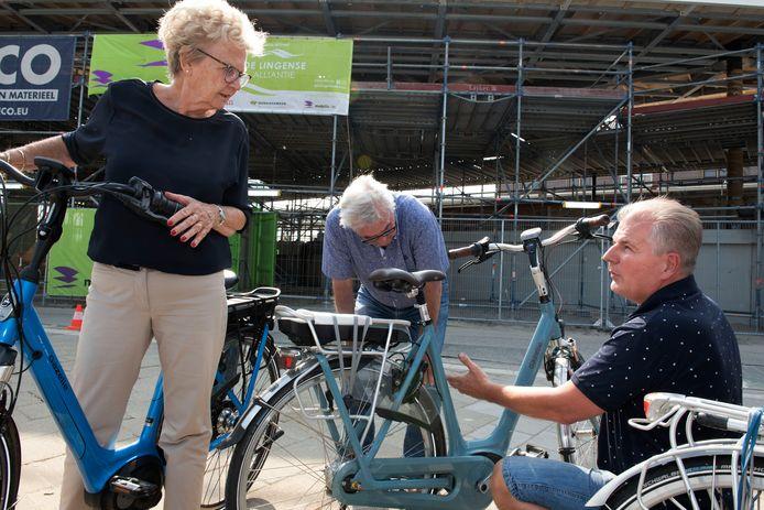 Fietsenmaker Kees van Zuijlen adviseert Riekie van Ooijen en Gerard Notenboom hoe ze hun elektrische fietsen beter kunnen beveiligen tegen diefstal.