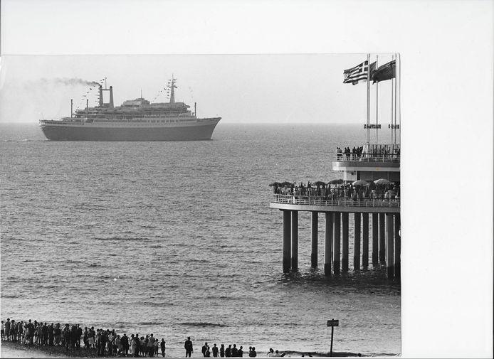 Het s.s. Rotterdam vaart begin jaren zestig langs de Pier. Het saat zwart van de mensen op het strand, de boulevard en op de Pier.