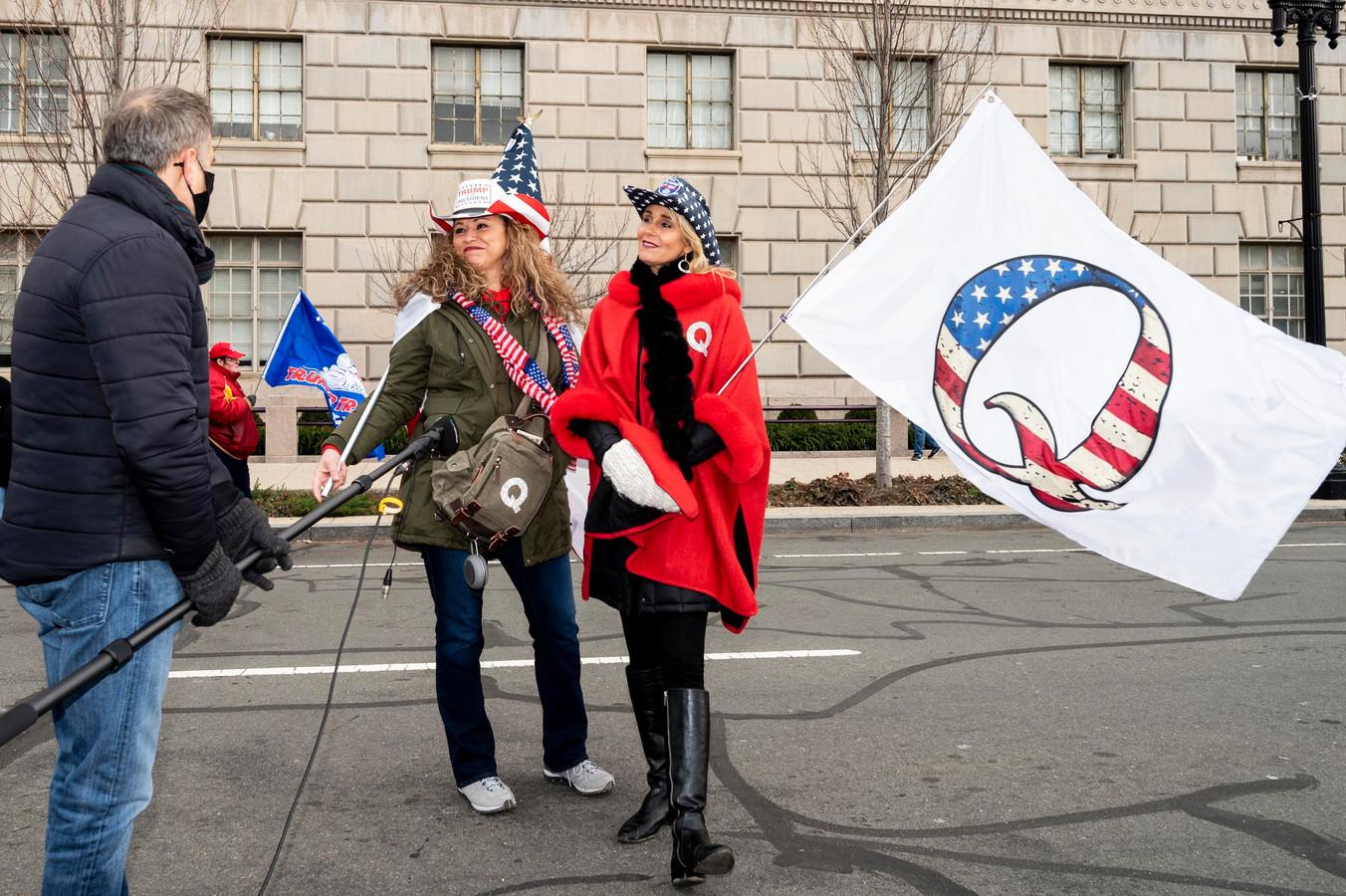 Een demonstrant met een vlag van de extreemrechtse complotgroep  QAnon.