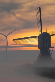 Herfstmist rond oude en nieuwe molens levert uniek beeld op