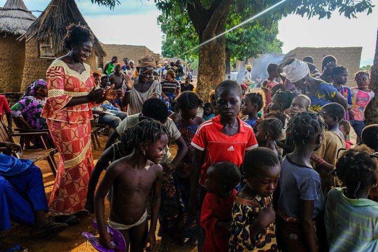 Lea Pare, hoofd voorlichting van Target Malaria, danst met kinderen in afwachting van het door haar ingehuurde theatercollectief. Beeld Joost Bastmeijer