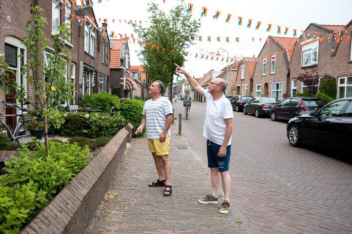 Willem van Londen (r) wijst buurman Max Laarman de scheuren in zijn gevel en tuinmuurtje in de Weststraat in Zierikzee aan. Volgens de bewoners komen de scheuren vooral van zwaar verkeer dat door de straat dendert.