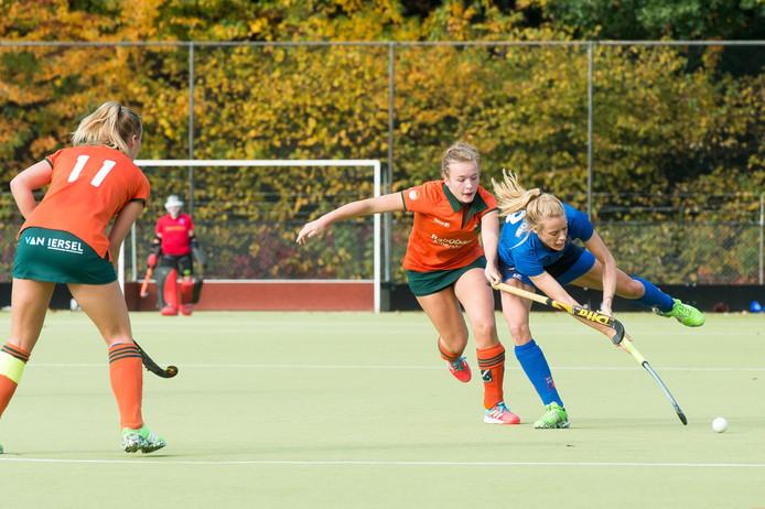 Scherp duel tussen Pam Ligtvoet van Warande (oranje) en Aniek van Loon van Breda. Links met nummer 11 Floor Steneker (Warande). Foto René Schotanus/Pix4Profs