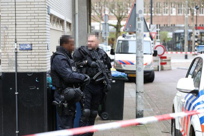 Politiemensen met automatische wapens staan voor het voormalige HBU-gebouw.