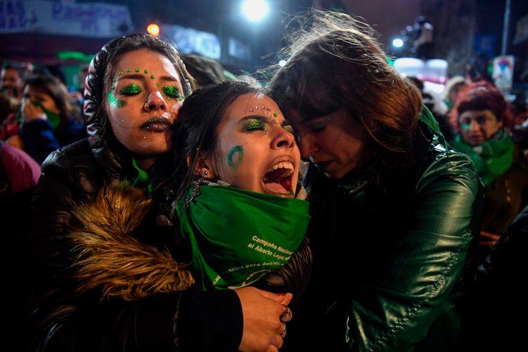 Voorstanders van de legalisering van abortus, getooid met groene sjaals, troosten elkaar woensdag in Buenos Aires nadat de Argentijnse Senaat de wet heeft verworpen. Beeld AFP