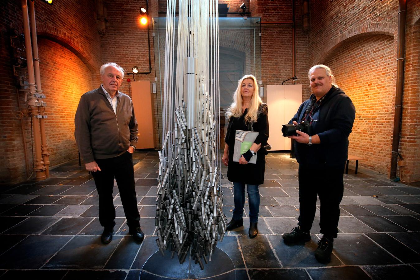 Piet IJssels, Annet Ardesch en Etienne Busink bij het kunstwerk van Corrie van de Vendel in herdenkings-, bezinnings- en ontmoetingscentrum In de Toren. Bezoekers kunnen in de koker een persoonlijk briefje achterlaten.
