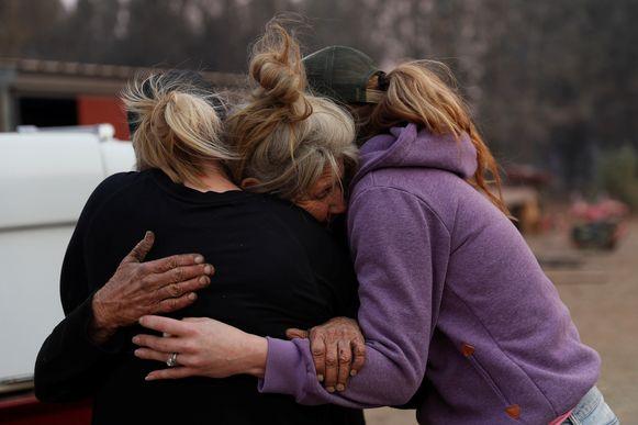 Cathy Fallon (midden) bleef achter in Paradise om voor haar tien paarden te zorgen, toen iedereen evacueerde. De twee vrouwen die haar omhelzen komen levensmiddelen brengen voor haar en de paarden.