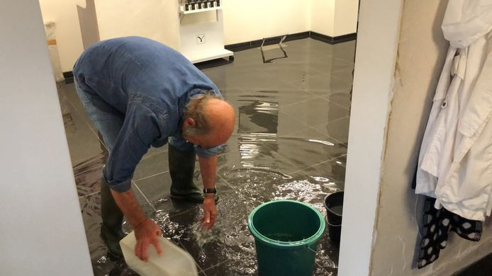 Ook in Tienen loopt het water binnen in huizen. Deze man doet er alles aan om zijn huis droog te houden.
