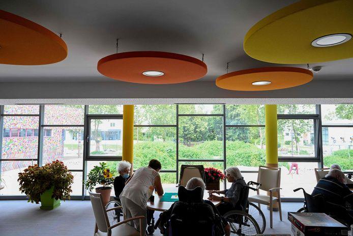 Des résidents âgés, assis autour d'une table, jouent à des jeux à l'EHPAD La Roselière à Kunheim, dans l'est de la France, le 2 août 2021.
