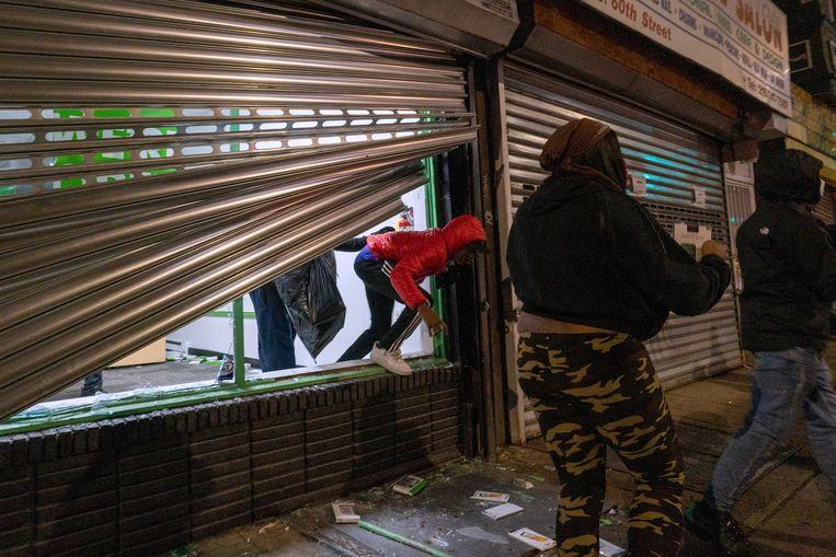 Plunderaars bij een opengebroken winkel in Philadelphia. Beeld REUTERS