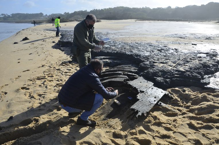 Archeologen inspecteren stukken wrakhout van een schip op het Portugese strand. Beeld Instituto de Arqueologia e Paleociências