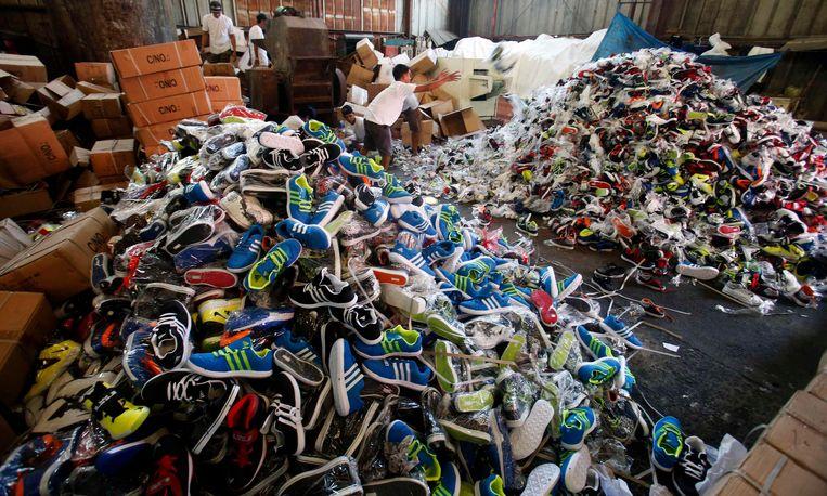 Een heleboel nepmerkschoenen op een hoop. Namaak is wereldwijd een probleem. Beeld REUTERS