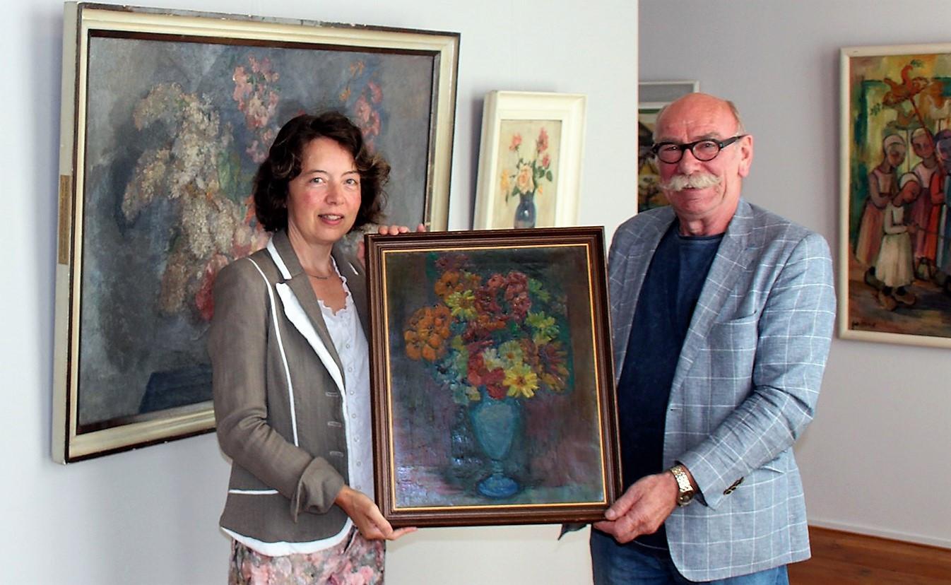 Conservator Mieke Mulders neemt het schilderij in ontvangst van Berrie Land.