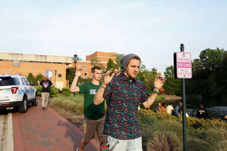 Studenten lopen met hun handen omhoog naar buiten.