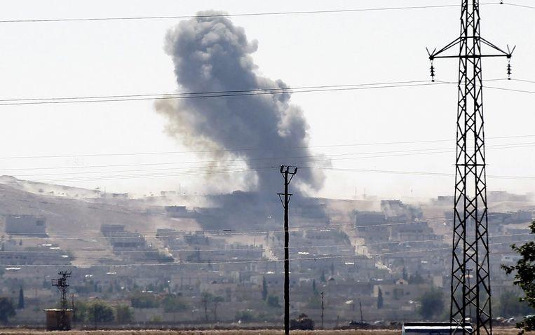 Een zwarte rookpluim boven Kobani, waar een flinke slag wordt geleverd. Beeld epa