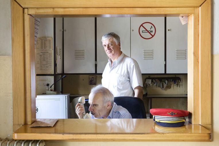Athanasios Demiris (staat recht) en zijn collega in hun kantoor aan het station van Drama, Griekenland. steeds minder treinen stoppen aan het station van Drama. Beeld Io Cooman