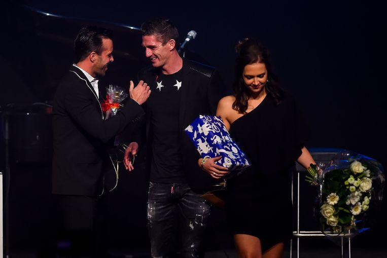Anthony Kumpen overhandigt Jurgen Van den Broeck zijn cadeau. VDB's vriendin Joke komt mee op het podium om bloemen te ontvangen.