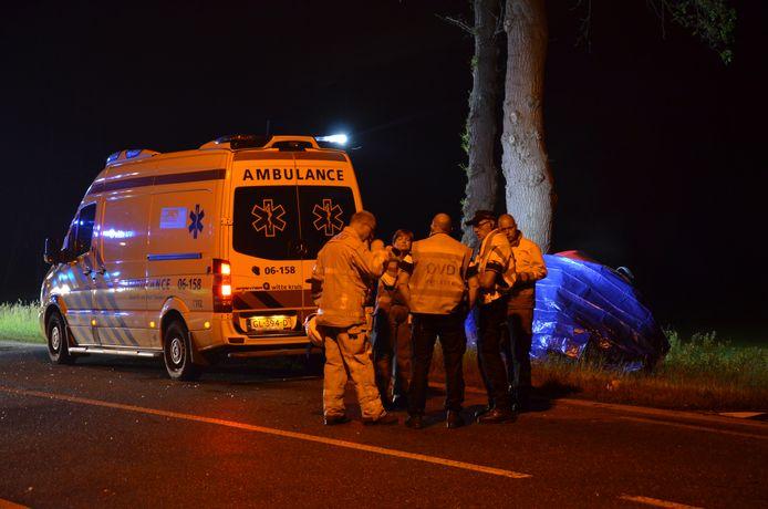 De hulpdiensten overleggen na het dodelijk ongeluk op de Nettelhorsterweg in Lochem. Het autowrak is ingepakt met een blauw zeil.