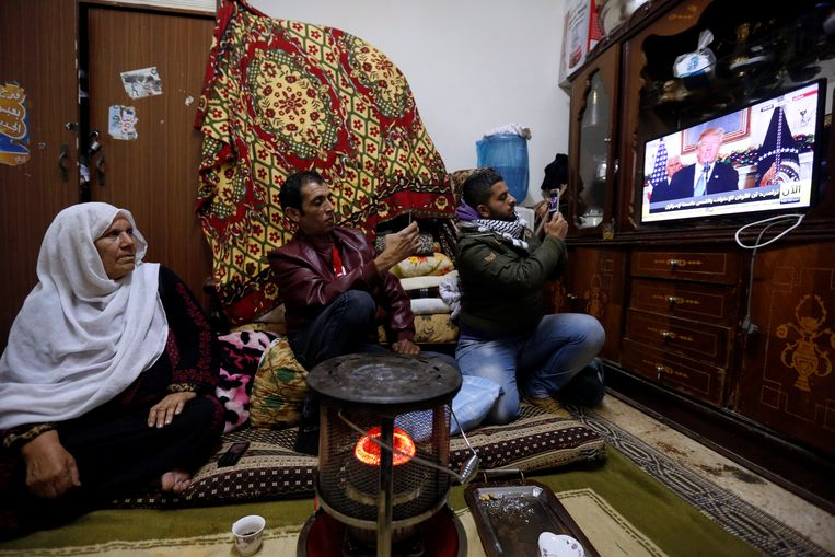 Een Palestijnse familie bekijkt de toespraak van president Trump in een vluchtelingenkamp in Jordanië.  Beeld REUTERS