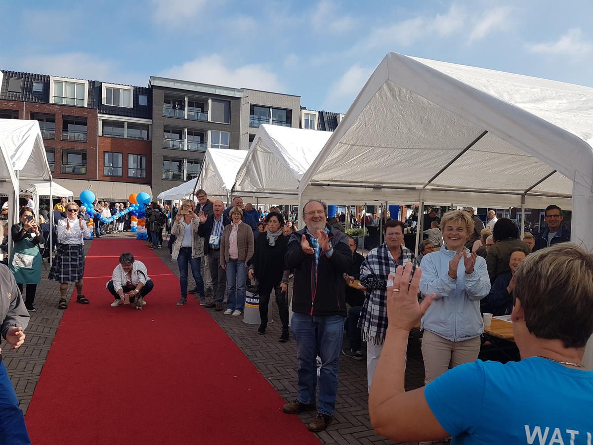 Lopers worden aangemoedigd door ontbijtende supporters op het Anton Pieckplein in het centrum van Kaatsheuvel.