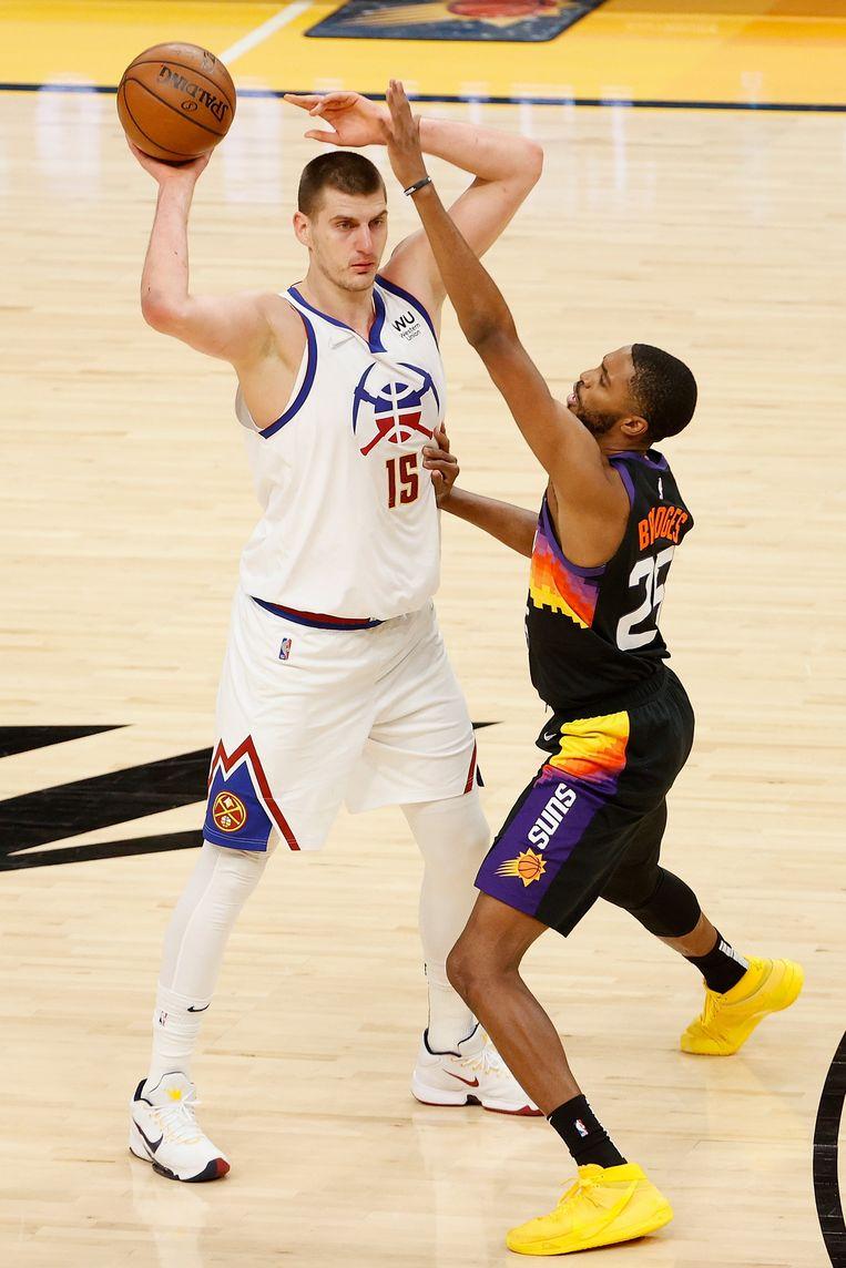 Nikola Jokic staat op het punt langs Mikal Bridges van Phoenix Suns te passen, 9 juni 2021.  Beeld AFP