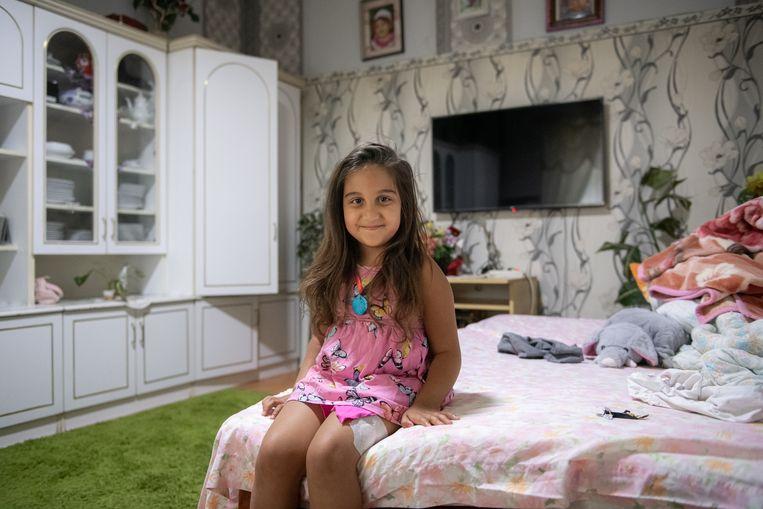 Meisje binnen in een van de oude huisjes van de staalarbeiders in het Hongaarse Hétes , waarin de Roma nu wonen. Ze deelt het bed met haar ouders en zusjes. Beeld Photo: Dénes Erdős