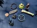 Een kleine selectie van de gevonden bodemschatten, waaronder een bronzen bel, een armband, het Silenuskopje, een zilveren leerbeslag en een Romeinse mantelspeld.