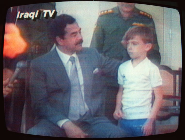 23 augustus 1990: Saddam Hoessein pakt Stuart vast voor het oog van de Iraakse tv-camera's.  Beeld Hollandse Hoogte / AFP