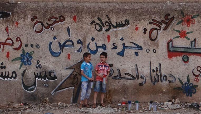 Op een graffitimuur in Saraqeb, de thuisstad van Iyas Kaadouni, staat een vredesboodschap: 'Syrie is onze thuis. Thuis is samen zijn. In vrede. Rechtvaardig. Met respect. In vrijheid. Hand in hand bouwen we een land. Ons droomland.' Beeld kos