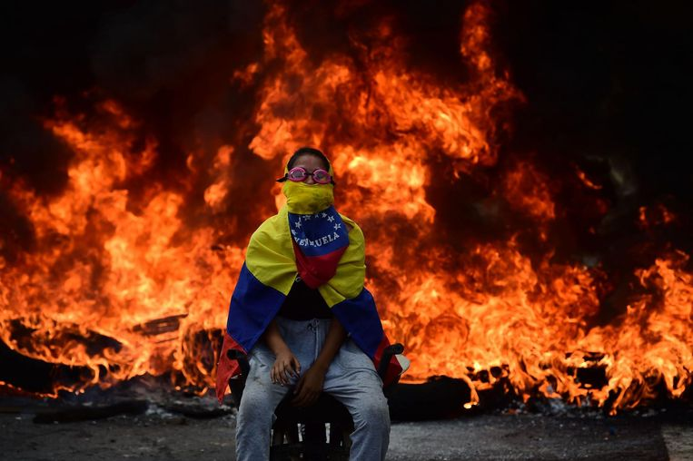 TOPSHOT - A Venezuelan opposition activist is backdropped by a burning barricade during a demonstration against President Nicolas Maduro in Caracas, on April 24, 2017. Protesters rallied on Monday vowing to block Venezuela's main roads to raise pressure on Maduro after three weeks of deadly unrest that have left 21 people dead. Riot police fired rubber bullets and tear gas to break up one of the first rallies in eastern Caracas early Monday while other groups were gathering elsewhere, the opposition said.  / AFP PHOTO / Ronaldo SCHEMIDT Beeld afp