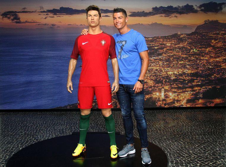 Cristiano Ronaldo poseert met een wassen beeld van zichzelf tijdens een bezoek aan het CR7-museum in juli 2016. Beeld EPA