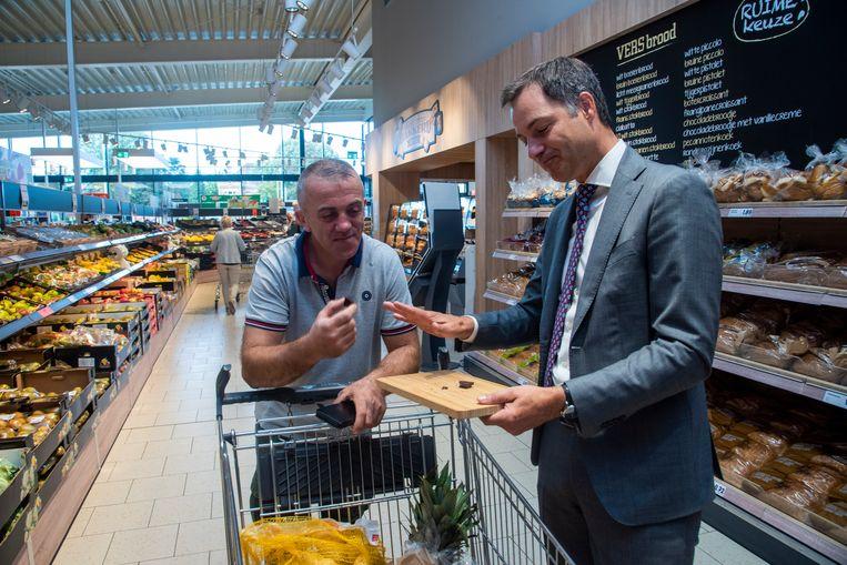 Minister van Ontwikkelingssamenwerking Alexander De Croo laat de klanten proeven van de Way To Go Fairtrade-chocolade.