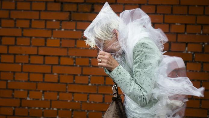 Een wandelaarster trotseert hevige windstoten. Foto ter illustratie.