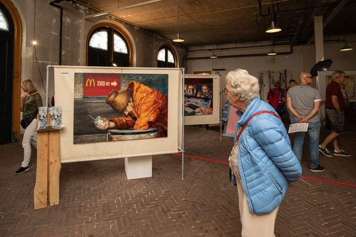Een bezoeker bekijkt een werk van Peter Schipper in de Koninklijke Stallen bij Paleis Soestdijk.