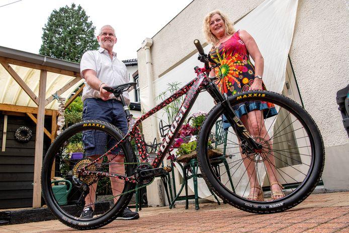 Paula en Wiebe Terpstra houden zich vast aan de mountainbike waarmee dochter Anne een wereldbekerwedstrijd won. Dinsdag komt zij voor de tweede keer in actie op de Olympische Spelen.