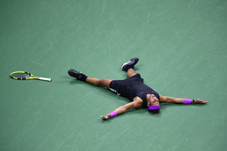 Uitgeput valt Nadal op zijn rug na het beslissende punt. Beeld Getty Images