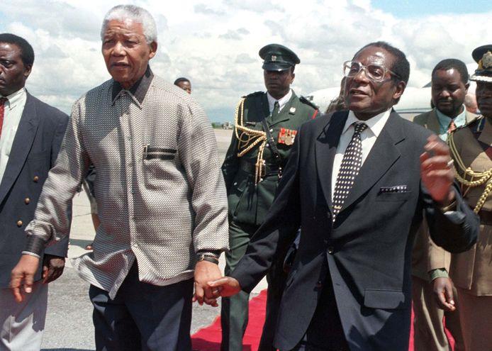 President Robert Mugabe hand in hand met president Nelson Mandela tijdens een staatsbezoek.