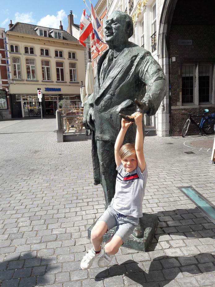 Florian van Overveld (6) bungelt aan de vingers van Anton van Duinkerken op de Grote Markt van Bergen op Zoom