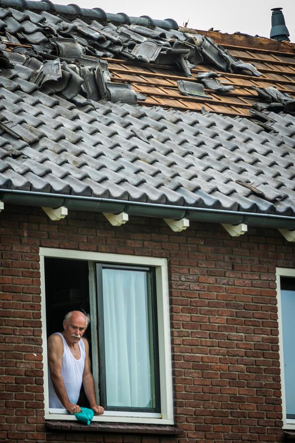 Een man praat in Rheden met zijn buurman. Op het dak is de schade van de storm duidelijk zichtbaar.
