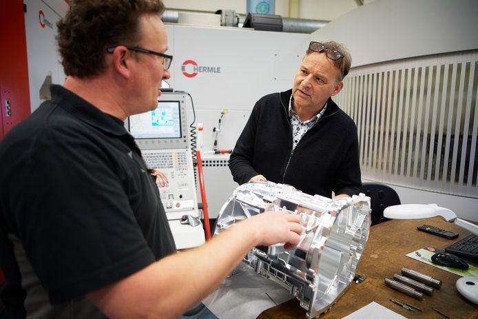 Jan Kusters (rechts) van Kusters Precision Parts en Kusters Beheer in gesprek met een medewerker over de behuizing van een versnellingsbak van een hybride auto.