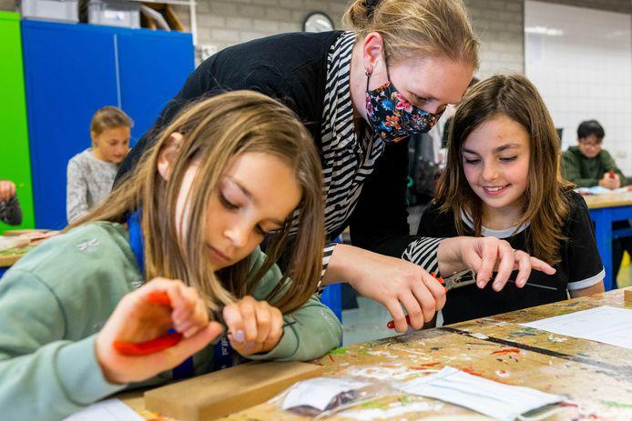 Liz Bekkers en Sanne van de Laak hebben elkaar al gevonden op de nieuwe Bossche tienerschool Spoor 10-14. Donderdag volgden ze een techniekles op de Bossche Vakschool. In het midden hun juf Stephanie.