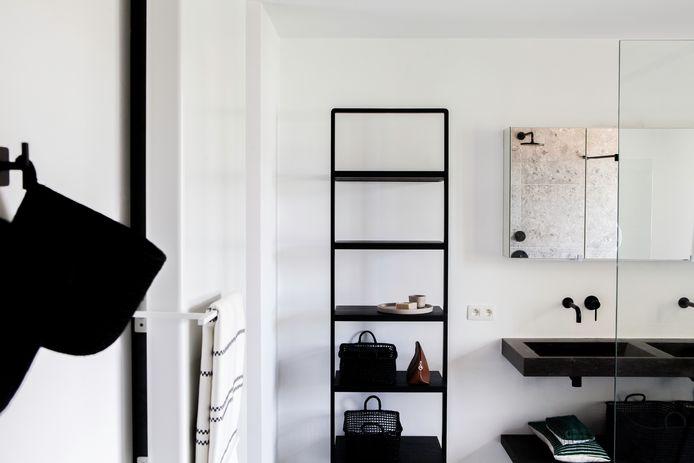 De badkamer oogt heel luchtig door de zwevende wastafel. Accessoires van D&M.