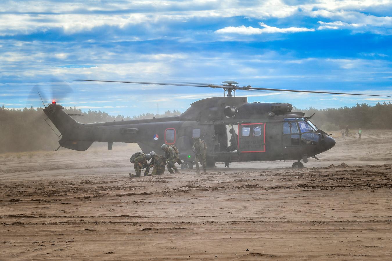 Militairen die op de grond wachten zijn door de brown out-landing volledig bedekt met stof.